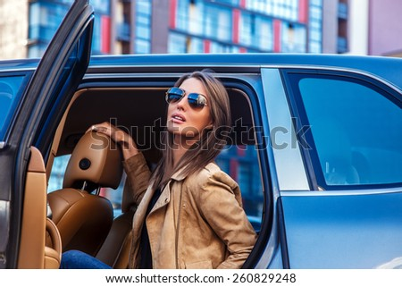 Awesome girl in sunglasses in a car back seats. - stock photo