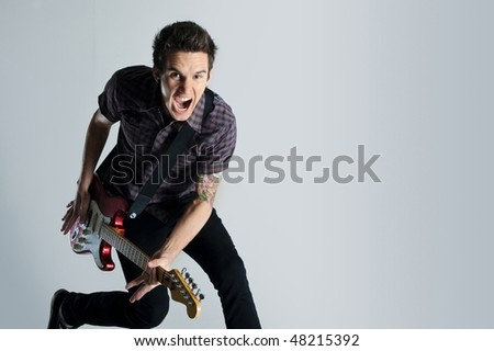 Awesome guitar player jumps with passion in studio