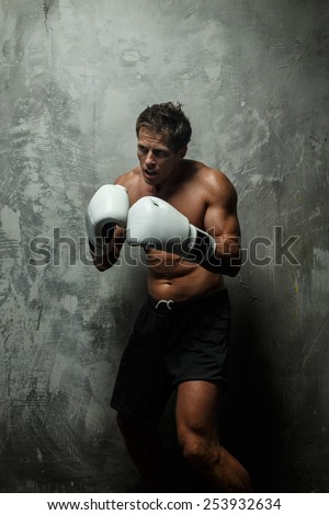 Awesome male with great body antomy boxing. Grey background. - stock photo