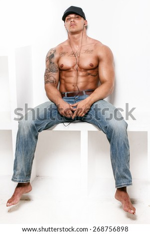 Awesome muscular guy in blue jeans and a cap on white background - stock photo