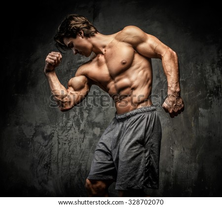 Awesome muscular man with great body posing over grey background. - stock photo