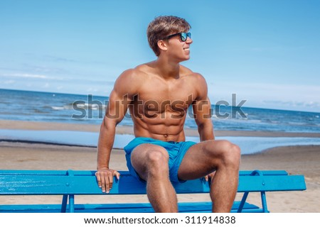 Awesome muscular young guy in blue swim shorts sitting on bench over blue sky and sea. - stock photo