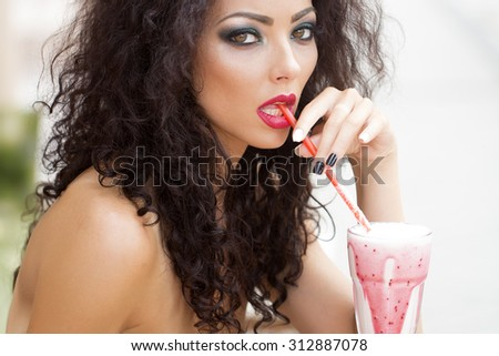 Awesome sensual magnificent young woman with bright makeup long brown curly hair with bare shoulders looking straight drinking cocktail through straw closeup on light background, horizontal picture - stock photo