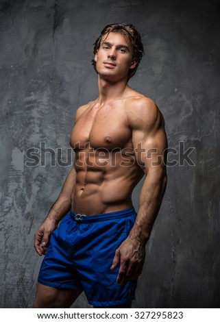 Awesome shirtless bodybuilder in blue shorts posing over grey background.