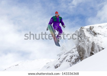 Awesome snowboarder jumps of a cliff in Les Portes du Soleil in France - stock photo