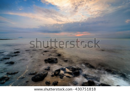 Awesome sunrise with marvelous clouds at Black Stone Beach, Kuantan, Malaysia.Slow shutter used to create foamy & hazy effect.