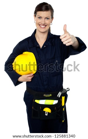 Awesome work by team. Woman in builder uniform showing thumbs up sign to camera. - stock photo