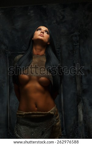 Awesome young woman in ancient armor on grey background. - stock photo