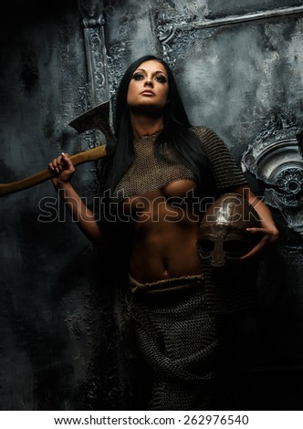 Awesome young woman in ancient armor with axe and helmet on grey background. - stock photo