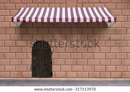 awning on brick wall with wooden old door - stock photo