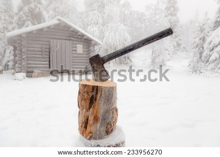 Ax stuck in log of wood on the background of the winter forest and