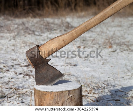 Axe and log in winter forest at sun day - stock photo