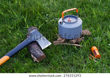 Axe, campfire kettle and matches. You can make tea or coffee on fire. Outdoor food items set. Travel, tourism and camping equipment. Picnic rest, cooking on the nature. Summer BBQ and grill tools.