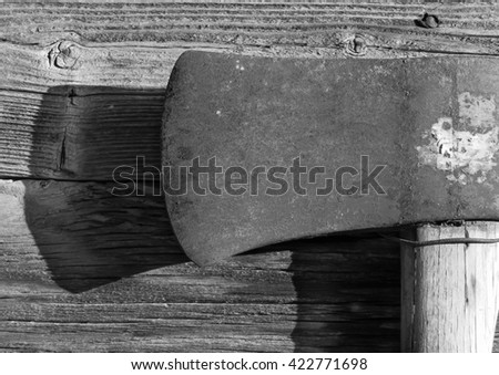 axe head close-up with interesting wood grain behind it - stock photo