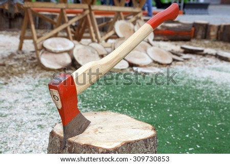 Axe in log with sawdust cut wood in background
