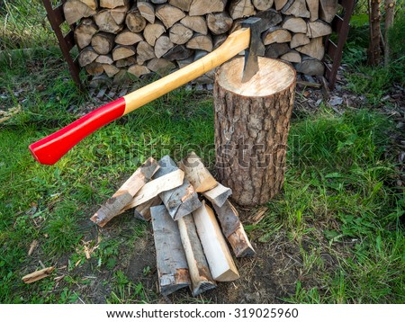 Axe on chopping block with chopped logs - stock photo