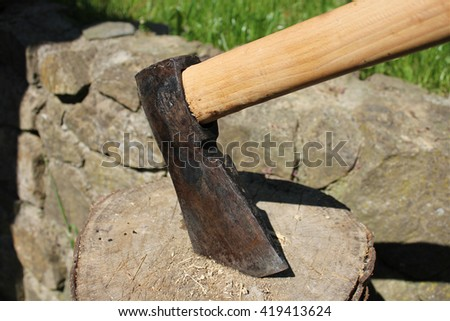 Axe stuck in the log, stone wall as background  - stock photo