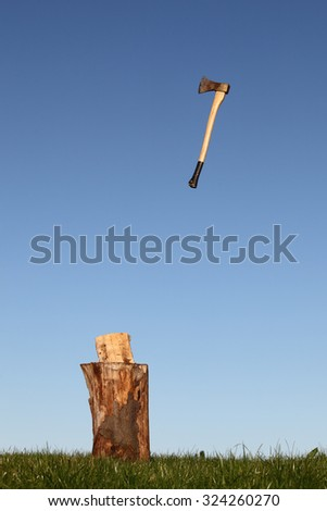 Axe to chop wood outdoors with blue sky - stock photo