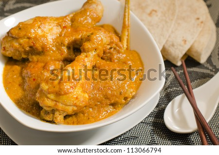 Ayam Kari Kapitan - Malaysian spicy chicken curry with coconut milk served with roti. Traditional Nyonya cuisine. Low key lighting. Close up. - stock photo