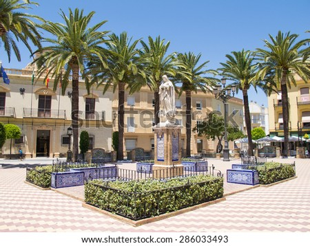 AYAMONTE, SPAIN - JUNE 4 2015 Pretty Laguna Square lined with palm trees and housing the town hall for Ayamonte. It is surrounded by cafes and is a regular meeting place for tourists and locals.