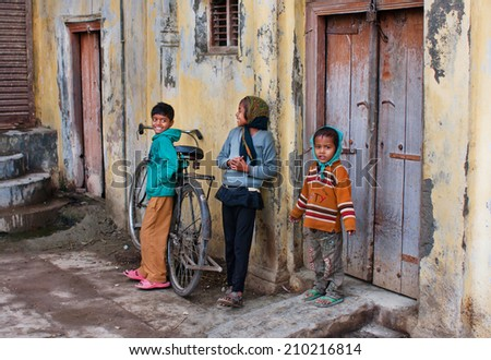 AYODHYA, INDIA - JAN 28: Unidentified children have fun with bicycle in a courtyard of poor house on January 28, 2013. Ayodhya had a population of 49,593. 12% of the population is under 6 years of age - stock photo