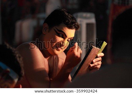 AYROOR, INDIA - JAN 08: An unidentified Kathakali artist does make-up before on-stage performance during a festival organised by District Kathakali club on January 08, 2016 in Ayroor, Kerala,India - stock photo