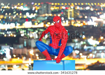Ayuttaya, Thailand - November 15, 2015 : Spider-Man model sit down on cityscape background. - stock photo