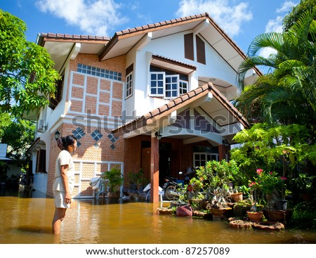 AYUTTHAYA - OCTOBER 9:  An unidentified women looks at her flooded house, because of a monsoon, on October 9, 2011 in Ayutthaya, Thailand. - stock photo