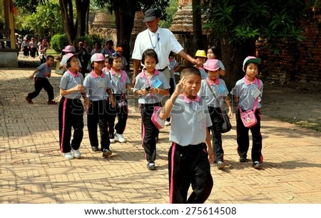 Ayutthaya, Thailand - December 20, 2010:   A group of Thai school children in their pink and black uniforms on a field trip with their teacher to historic Wat Phra Si Sanphet - stock photo