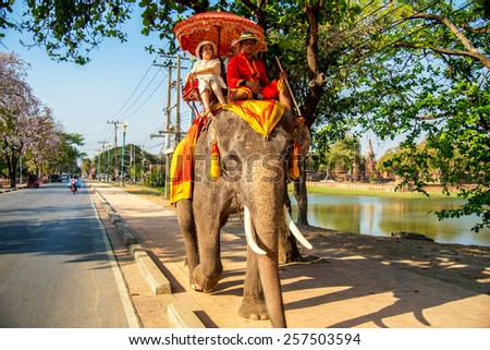 AYUTTHAYA, THAILAND - FEB 24: Tourists on an elephant ride tour of the ancient city on Febuary 24, 2015 in Ayutthaya.