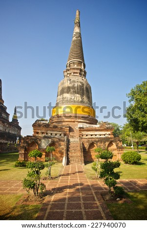 AYUTTHAYA, THAILAND - JANUARY 03, 2014: Sunken ancient Thai temple in perspectivic view at Wat Yai Chai Mongkol UNESCO World Heritage Site. Built in 1357 the stupa is a building from the old capital.
