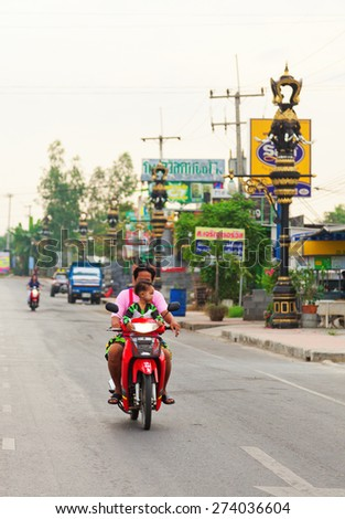 Ayutthaya, Thailand - March 09, 2011 : Father and young boy riding a motorcycle on a street in Ayutthaya - stock photo
