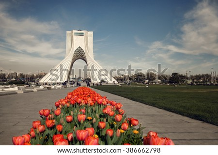 Azadi monument behind a row of red tulips in Tehran on springtime, edited with brown vintage filter. - stock photo