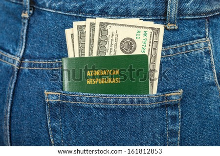 Azerbaijan passport and dollar bills in the back jeans pocket
