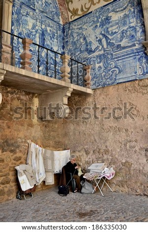 Azulejos and old lady in Obidos, Portugal . Obidos, Portugal - July 16, 2011.