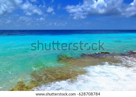 Azure and turquoise (cyan) tropical ocean. Small waves and white water spray. Coral reef underwater. Sunny day, blue sky and small clouds. Exotic calm vacation near a warm spring sea.