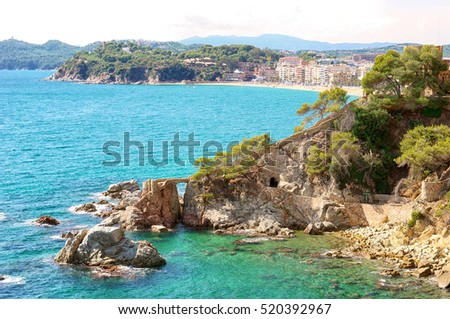 Azure bay harbor with crystal clear mediterranean water, which offers incredible views of the city beaches. Lonely rock on the waves with old bridge gate. Lloret de Mar, Spain, Europe.