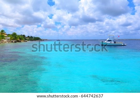 Azure cyan calm tropical ocean with beautiful pebble shore and scuba diving ship. Vacation by the romantic blue ocean with palm trees and ship. Azure water surface and sunny day with clouds.
