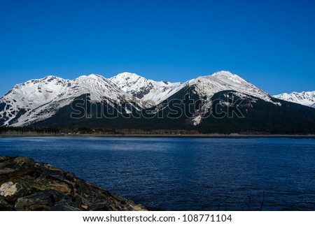 Azure Sky and Snow Capped Mountains Around the Turnagain Arm.  From the Seward Highway (1) Near Anchorage, Alaska.  The Great Alaskan Wilderness.  A Beautiful Landscape of Rock, Snow, Water and Ice. - stock photo