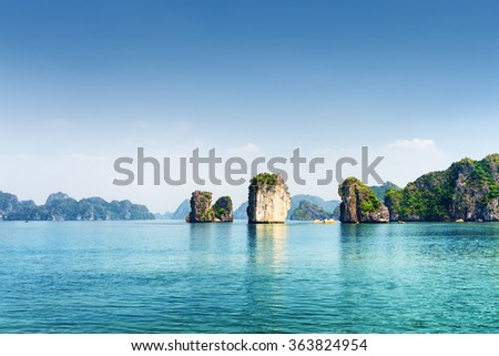 Azure water of the Ha Long Bay at the Gulf of Tonkin of the South China Sea, Vietnam. Beautiful view of blue lagoon and karst towers-isles. The Halong Bay is a popular tourist destination of Asia. - stock photo