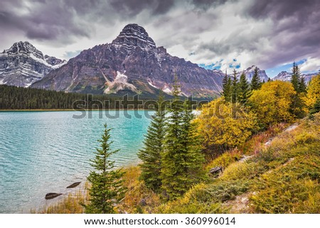 Azure waters of the river are surrounded with Rocky Mountains and magnificent yellow and orange vegetation. Autumn Bow River in Banff National Park, Canada - stock photo