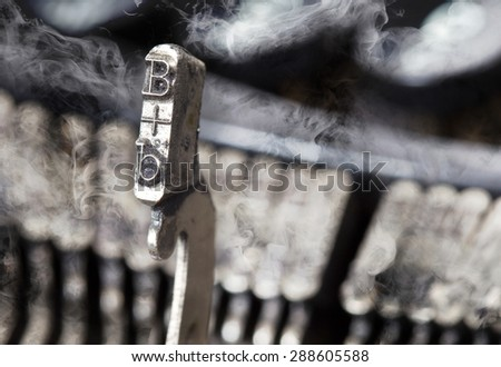 B hammer for writing with an old manual typewriter - mystery smoke - stock photo