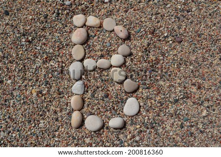B letter made of stones on sand - stock photo