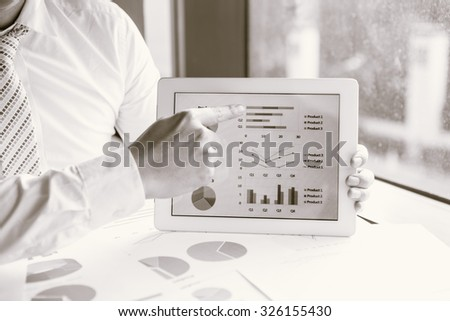 B&W / Business man meeting/present on tablet to discuss the situation on the market with product this year. - stock photo
