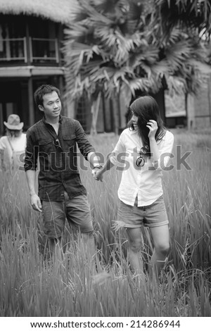 B&W / Cheerful young newlyweds hugging tenderly in bright countryside