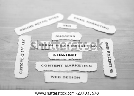 B/W focusing of strategy paper rip with soft style on wood background - stock photo