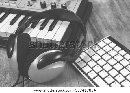B&W headphone, synthesizer and computer keyboard on wooden table for music composer concept background - stock photo