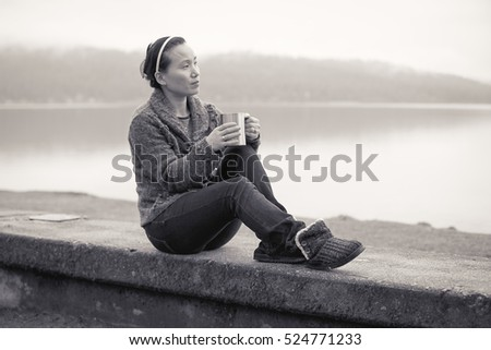 B&W of woman relaxing by lake.