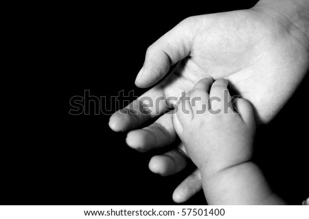 B&W photo of new-born baby hand in mother's palm, isolated on black background. - stock photo