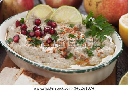 Baba ghanoush, levantine eggplant dish with lemon and pomegranate seeds - stock photo